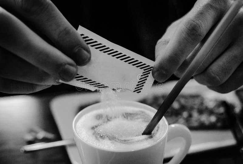 Hombre que añade el azúcar al café fotografía de archivo libre de regalías