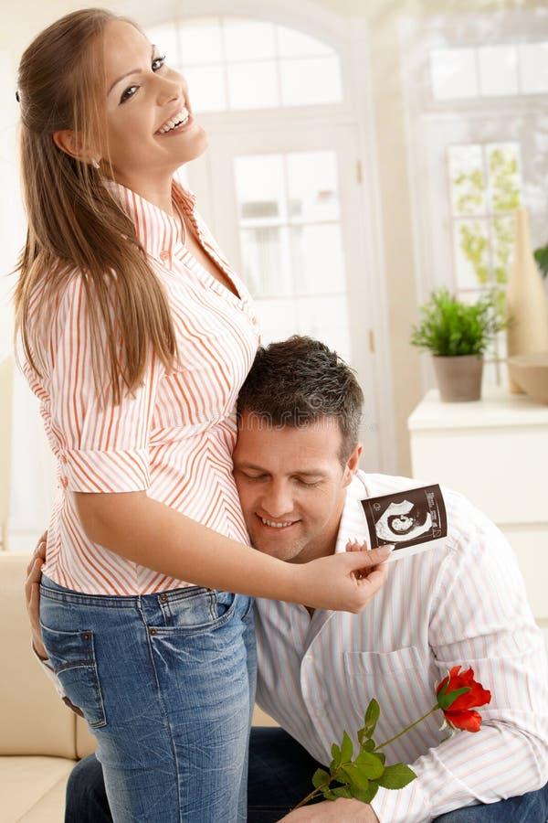 Hombre que abraza a la mujer embarazada imágenes de archivo libres de regalías