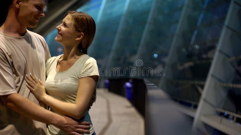 Hombre que abraza a la mujer en la tarde romántica cerca del centro comercial de la ciudad, fechando, primer imágenes de archivo libres de regalías