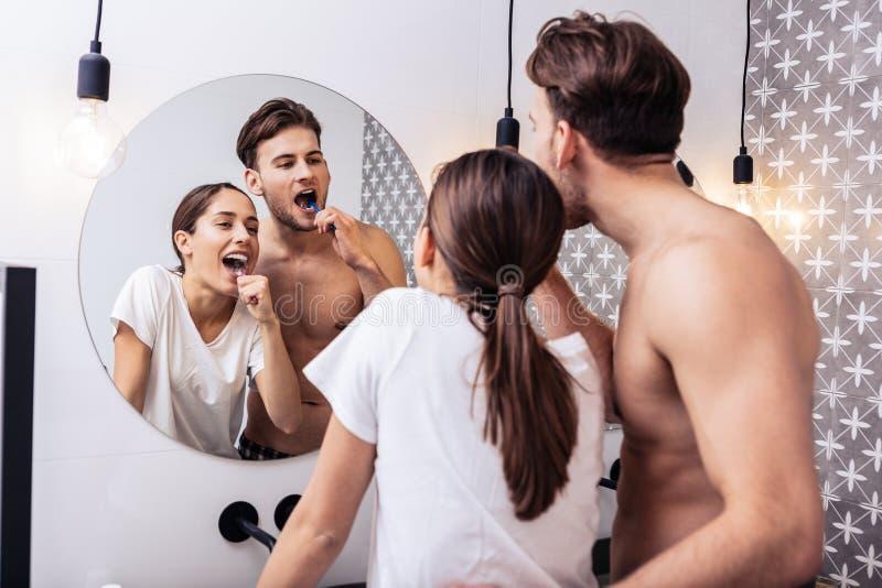 Hombre que abraza a su esposa preciosa mientras que cepilla los dientes juntos imagen de archivo libre de regalías
