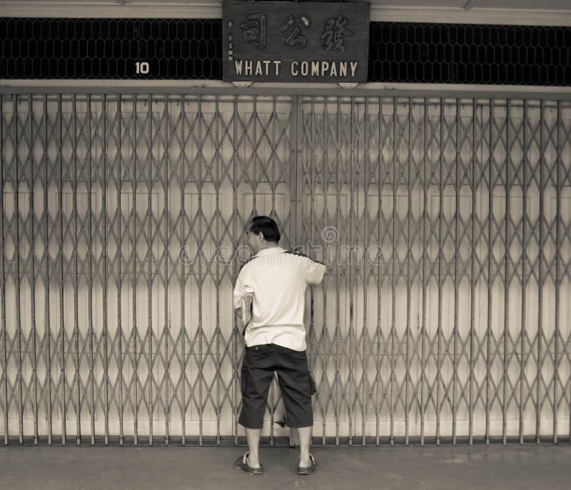 Hombre que abre la puerta del metal de su casa de la tienda en la calle de Kuching, Malasia imagen de archivo