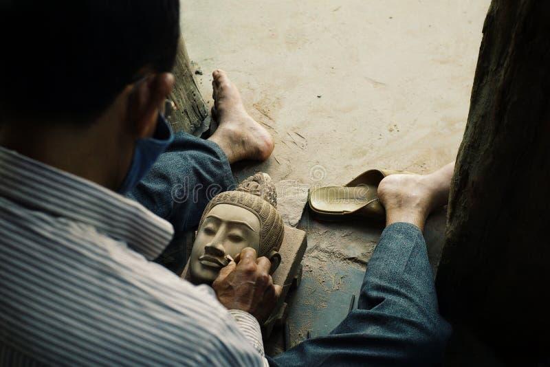 hombre que acaba una escultura de la cabeza de Buda como parte del proyecto de la restauración en las ruinas del templo imagenes de archivo