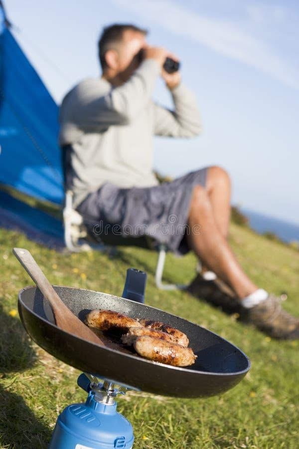 Hombre que acampa al aire libre y que cocina imágenes de archivo libres de regalías