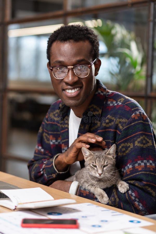 Hombre que acaricia un gato para reducir la tensión foto de archivo