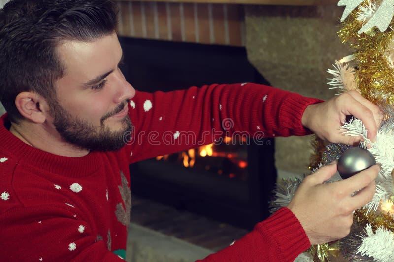 Hombre que adorna un árbol de navidad imagenes de archivo