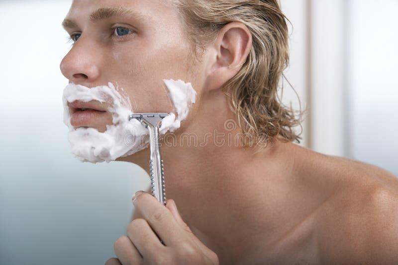 Hombre que afeita en cuarto de baño foto de archivo libre de regalías