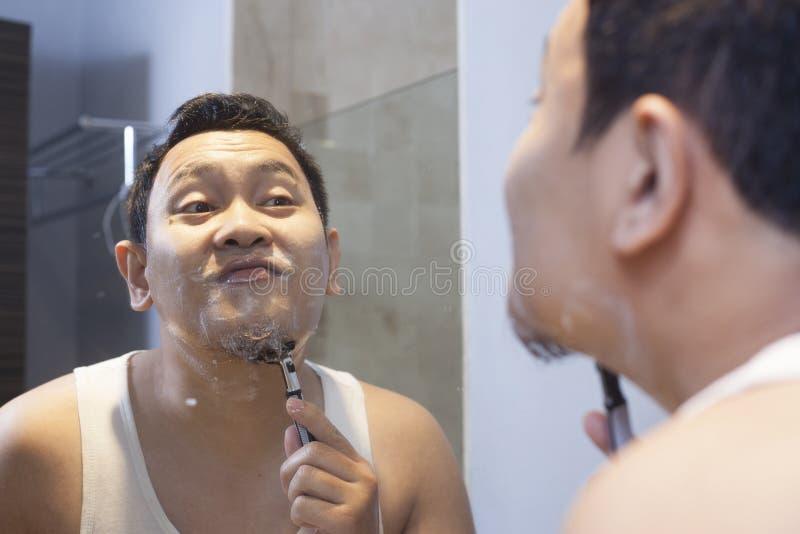 Hombre que afeita en cuarto de ba?o fotografía de archivo libre de regalías