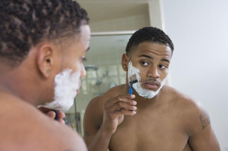Hombre que afeita en Front Of Bathroom Mirror imagen de archivo libre de regalías