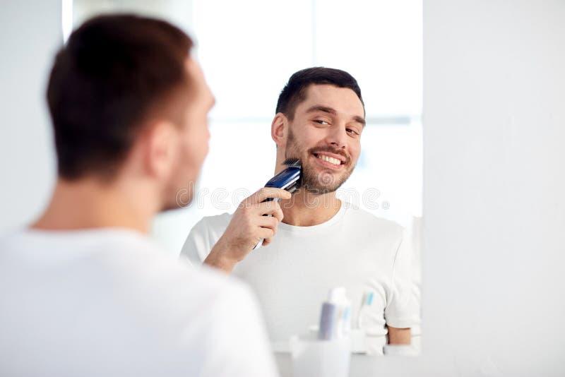 Hombre que afeita la barba con el condensador de ajuste en el cuarto de baño imagen de archivo