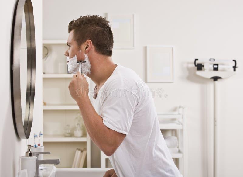 Hombre que afeita la cara foto de archivo