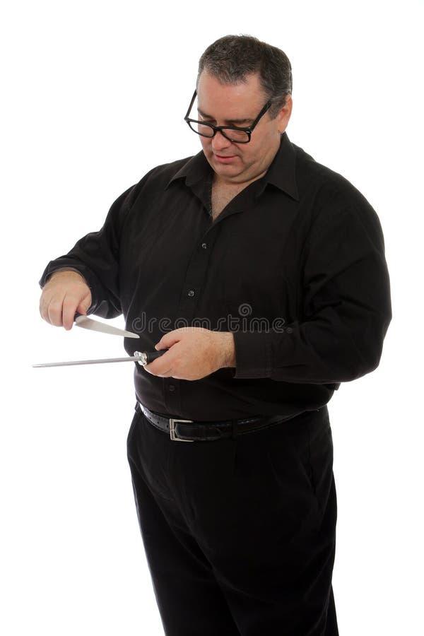 Hombre que afila un cuchillo imagen de archivo
