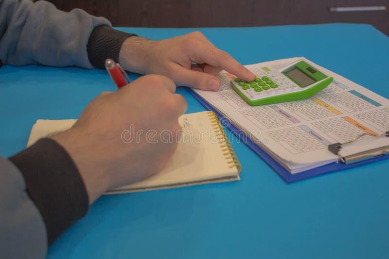 Hombre que analiza estad?sticas Las calculadoras, los propietarios de negocio, la contabilidad y la tecnolog?a, negocio foto de archivo libre de regalías