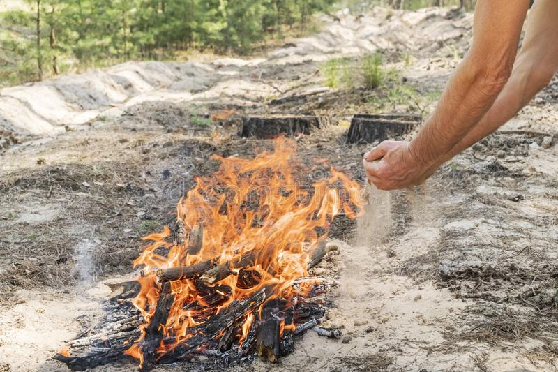 Hombre que apaga un fuego con la arena fotos de archivo libres de regalías