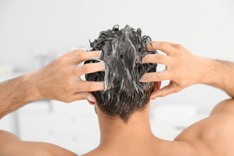 Hombre que aplica champú sobre su pelo imagen de archivo