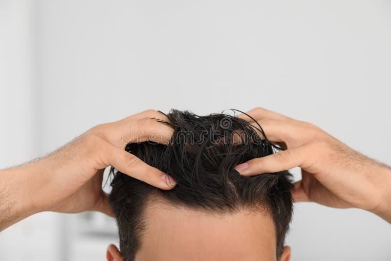 Hombre que aplica el acondicionador de pelo contra fondo ligero imagen de archivo