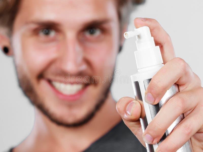 Hombre que aplica el cosmético del espray a su pelo fotografía de archivo libre de regalías