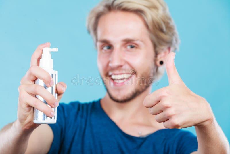 Hombre que aplica el cosmético del espray a su pelo foto de archivo