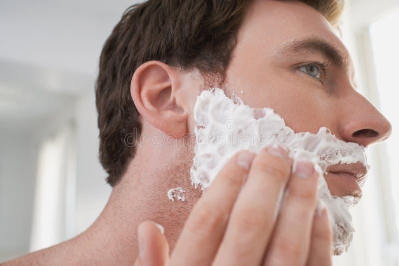 Hombre que aplica la crema de afeitar foto de archivo libre de regalías