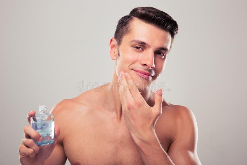 Hombre que aplica la loción después de afeitado en cara imágenes de archivo libres de regalías