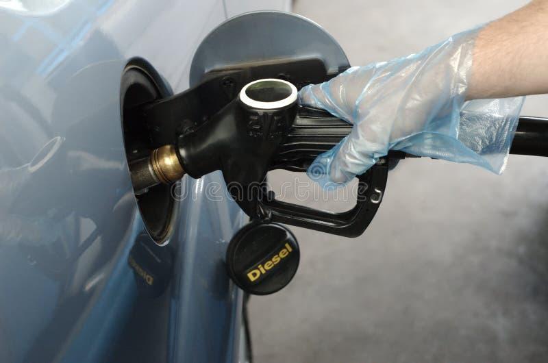 Hombre que aprovisiona de combustible el coche con diesel fotografía de archivo