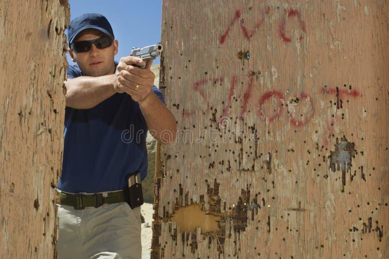 Hombre que apunta el arma de la mano a la gama de leña foto de archivo libre de regalías