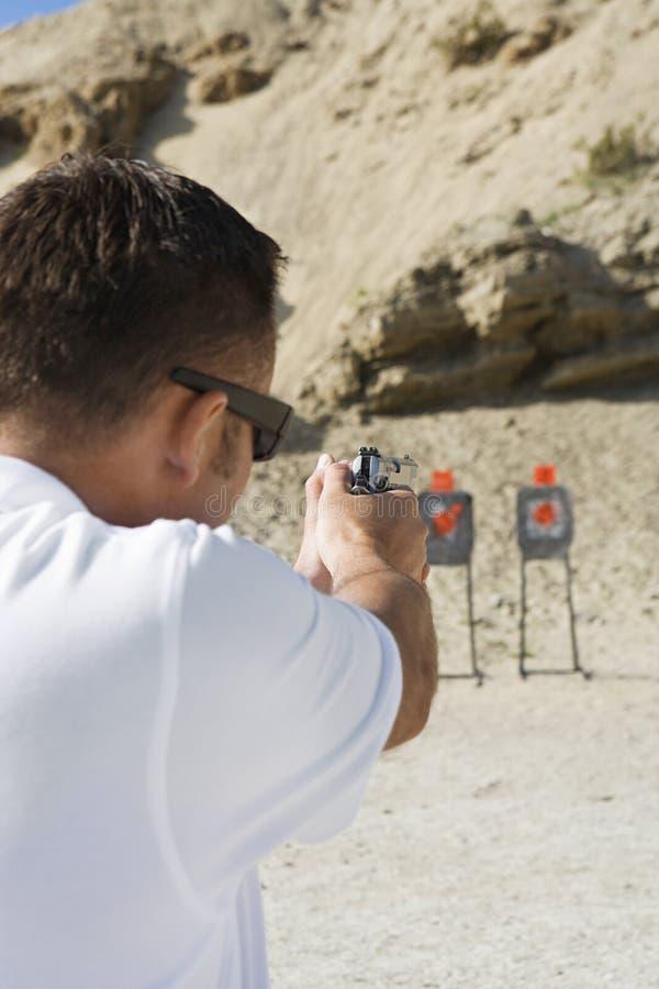 Hombre que apunta el arma de la mano a la gama de leña fotografía de archivo