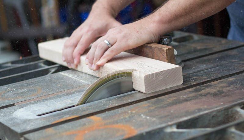 Hombre que asierra un pedazo de madera para un proyecto de DIY fotos de archivo