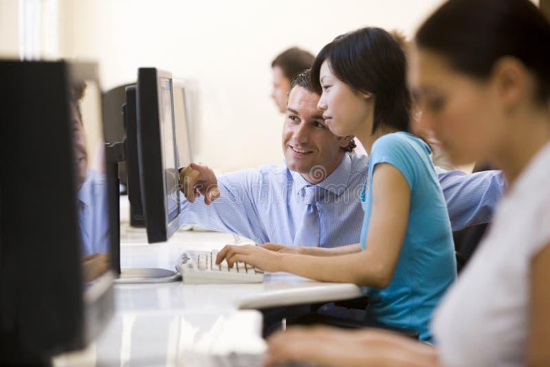 Hombre que asiste a la mujer en la sonrisa de la sala de ordenadores imágenes de archivo libres de regalías