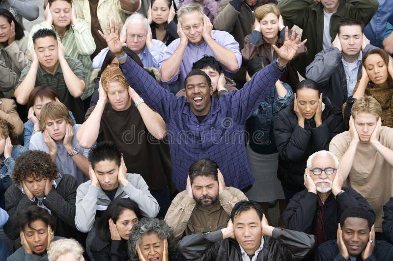 Hombre que aumenta las manos mientras que gente que cubre sus oídos imagen de archivo libre de regalías
