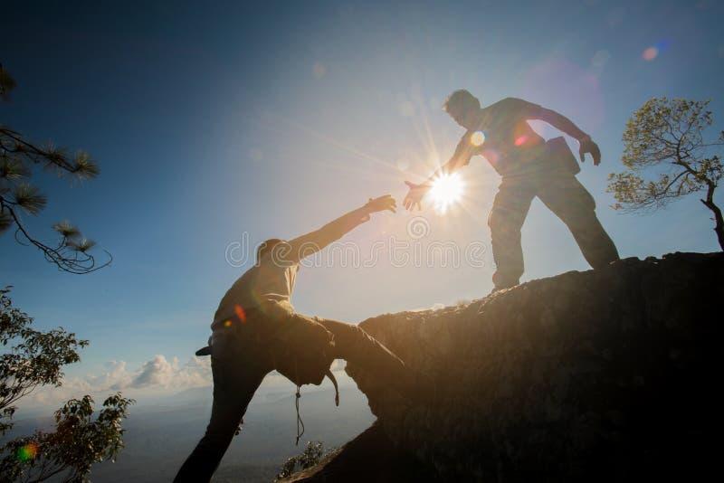 Hombre que ayuda a subir la roca fotografía de archivo libre de regalías