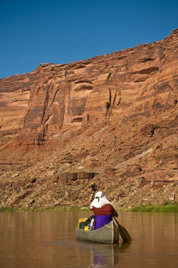 Hombre que bate la canoa en el río del cañón del desierto fotos de archivo