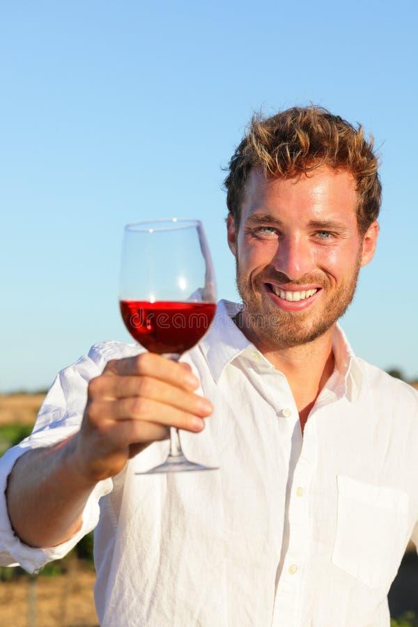 Hombre que bebe tostar del vino color de rosa o rojo fotografía de archivo libre de regalías