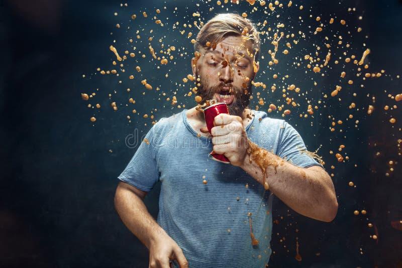 Hombre que bebe una cola y que disfruta del espray fotografía de archivo