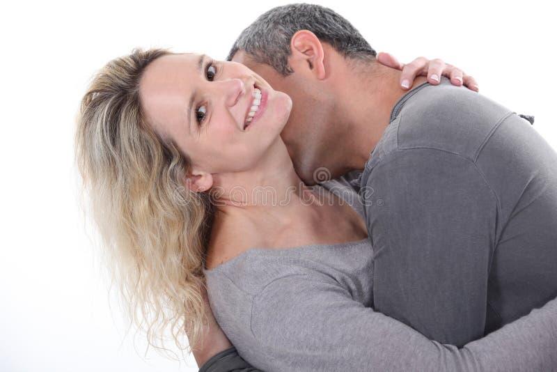 Hombre que besa el cuello de la esposa imagenes de archivo