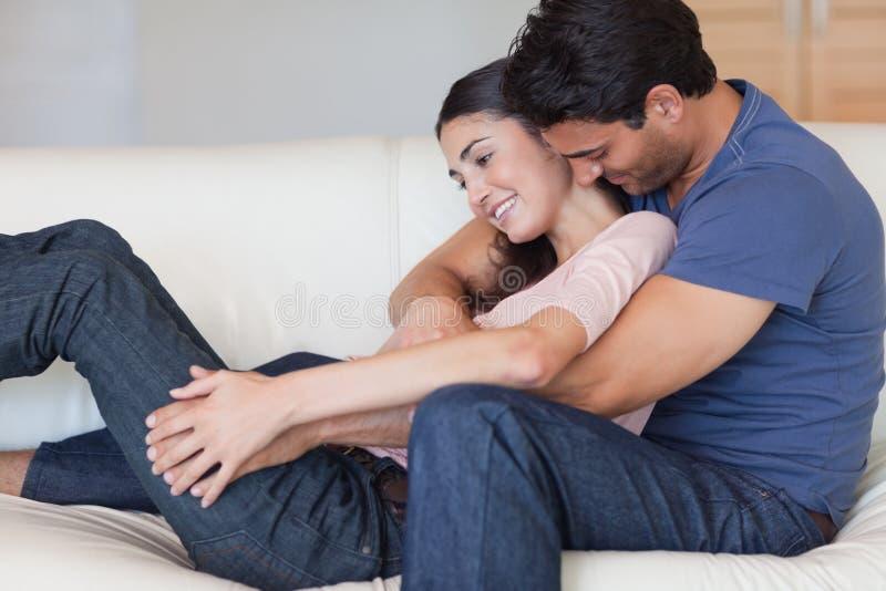 Hombre que besa a su novia en el cuello imagenes de archivo