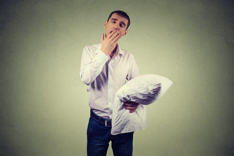 Hombre que bosteza con una almohada a disposición Privación del sueño, quemadura foto de archivo libre de regalías