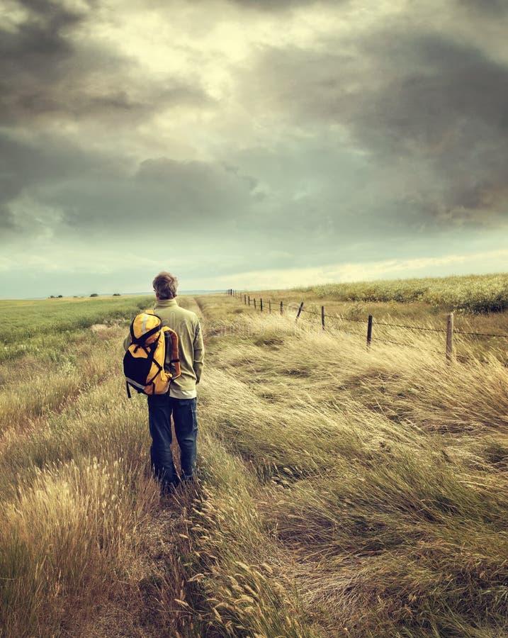 Hombre que camina abajo de la carretera nacional fotografía de archivo