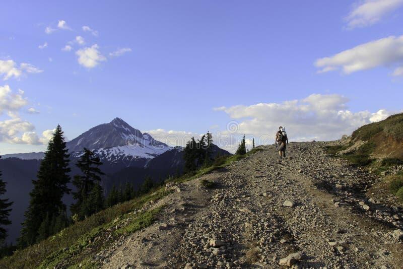 Hombre que camina al top del papel pintado de la montaña imagen de archivo libre de regalías