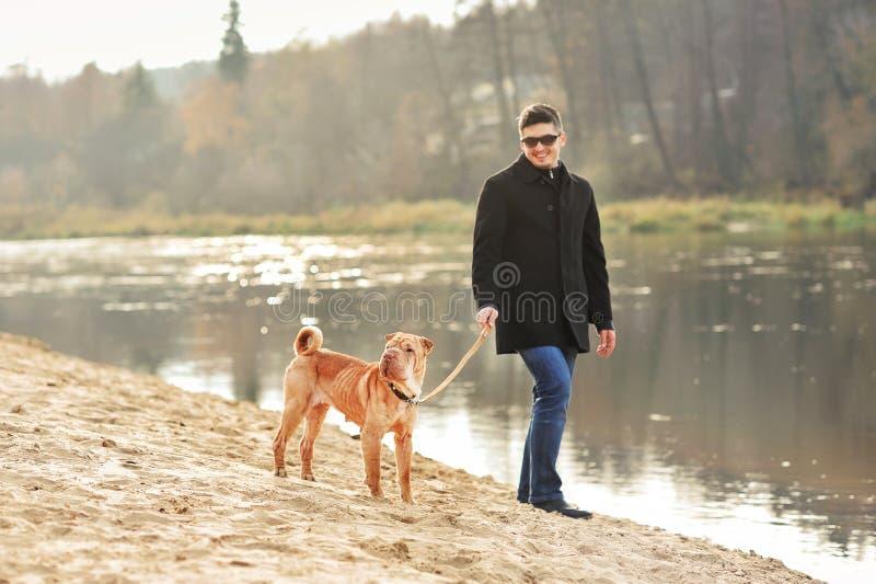 Hombre que camina con el perro cerca del río imagen de archivo libre de regalías