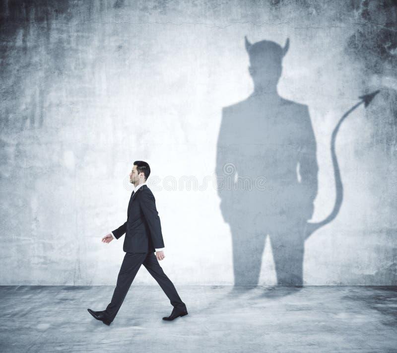 Hombre que camina con la sombra del diablo imagen de archivo