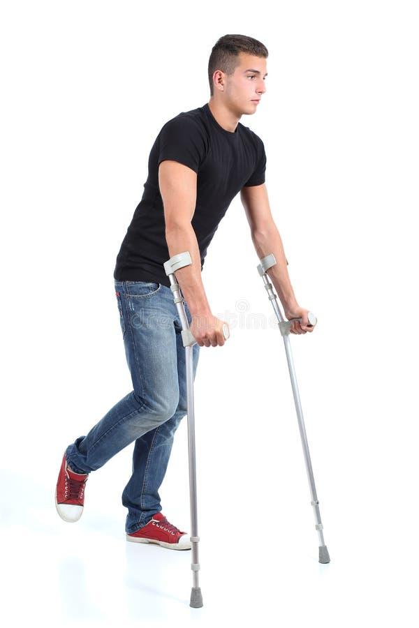 Hombre que camina con las muletas imagen de archivo libre de regalías