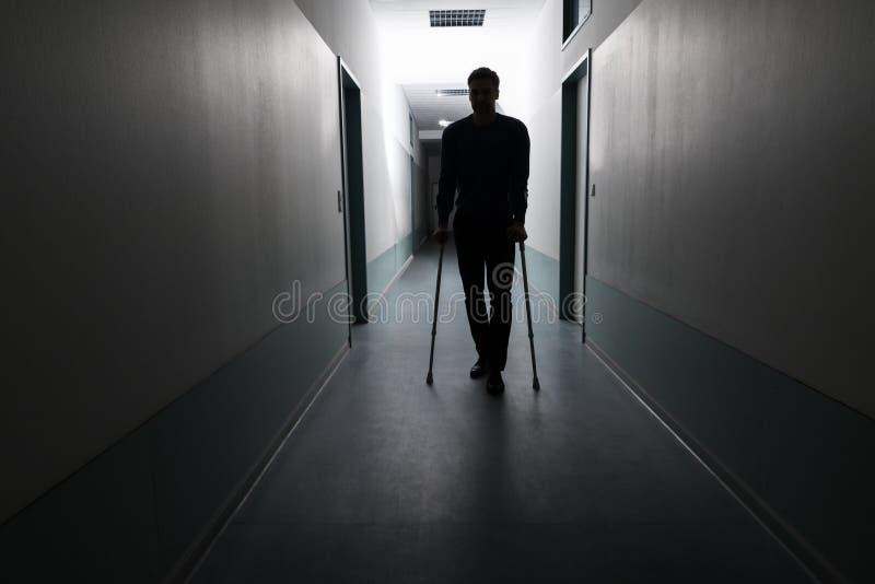 Hombre que camina con las muletas imagen de archivo