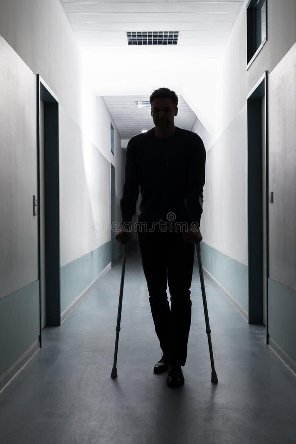 Hombre que camina con las muletas foto de archivo