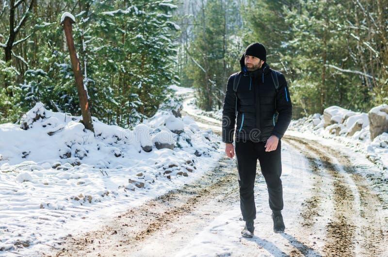 Hombre que camina en bosque nevoso del invierno fotos de archivo libres de regalías