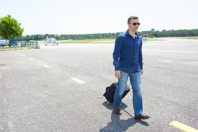 Hombre que camina en el aeropuerto que tira de la maleta fotos de archivo