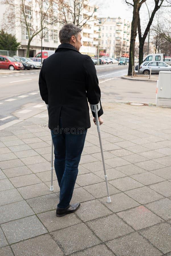 Hombre que camina en la calle usando las muletas foto de archivo