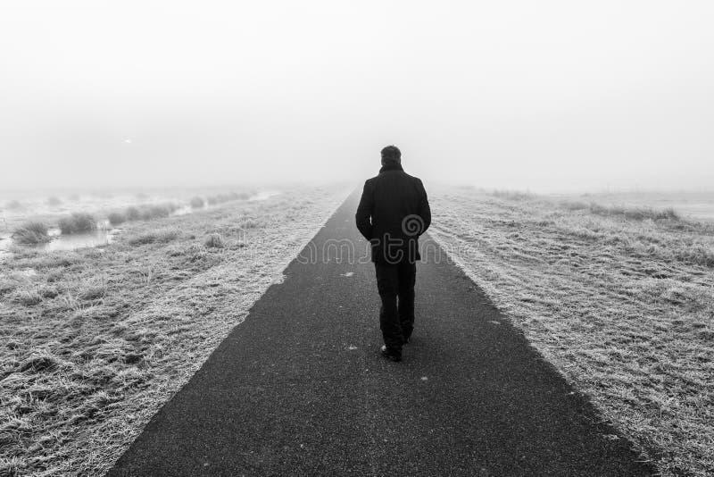 Hombre que camina en un raod solitario vacío imagen de archivo libre de regalías