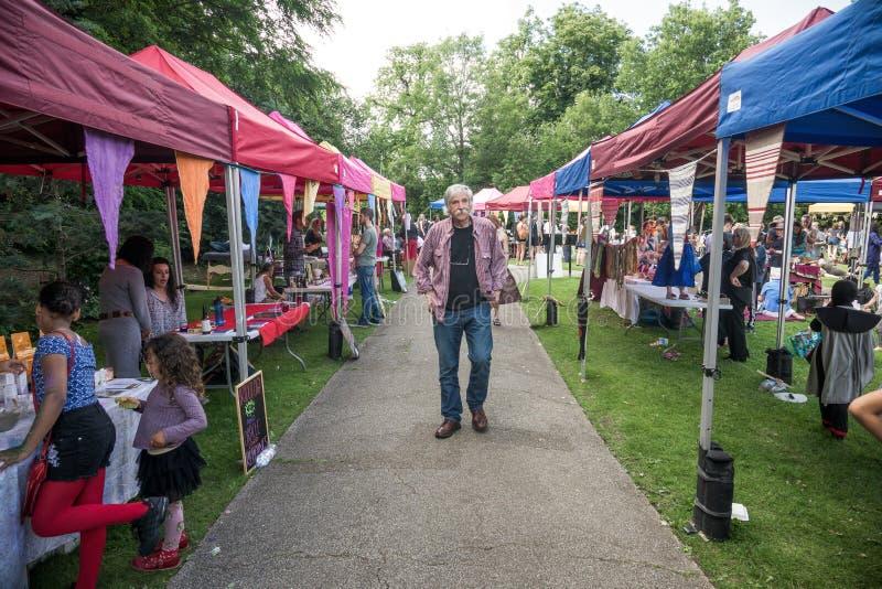 Hombre que camina entre paradas en el mercado imágenes de archivo libres de regalías