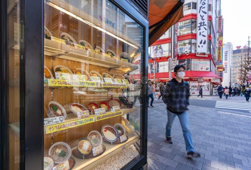 Hombre que camina más allá de un japonés en Tokio imagenes de archivo
