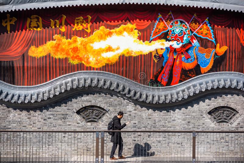 Hombre que camina por un fresco pintado de un artista chino de la ópera del spitter del fuego imágenes de archivo libres de regalías